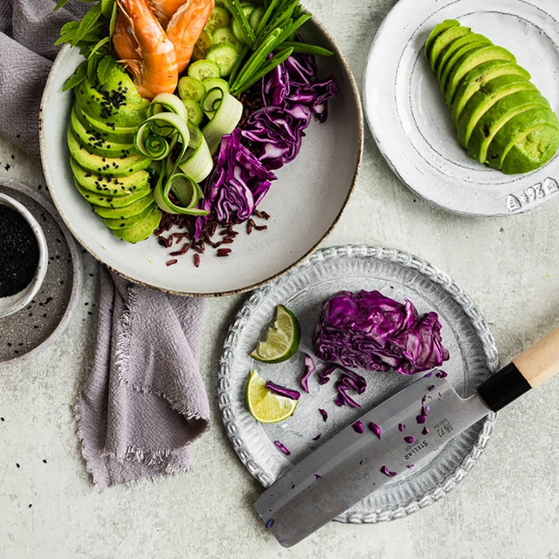 avocado and black rice bowl with knife on plate